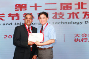Dr. Qiu presents Dr. Gupta with certificate